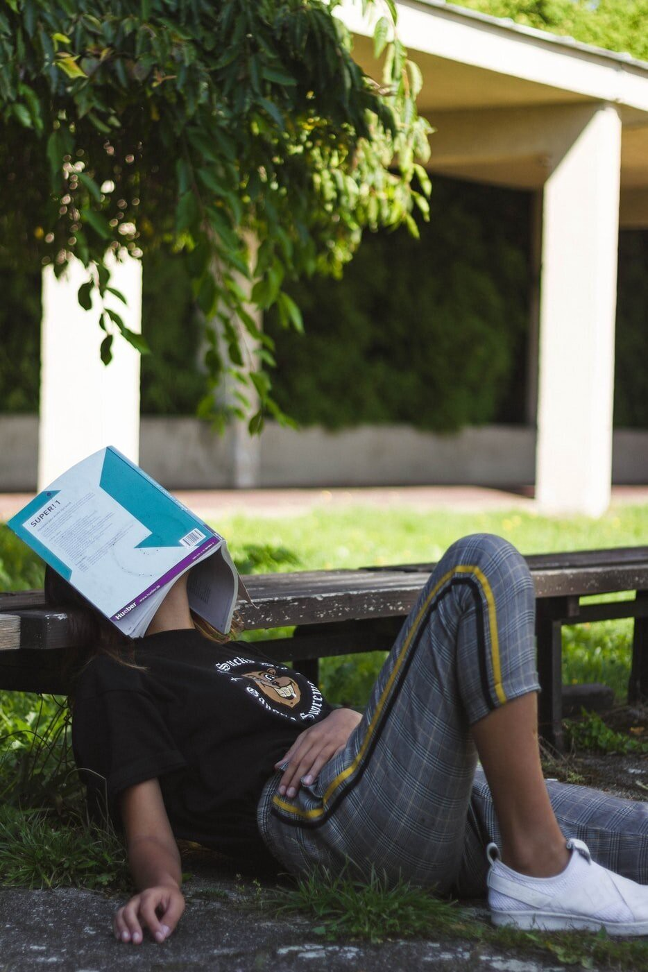 A student sleeps in the grass with a textbook folded over her face.