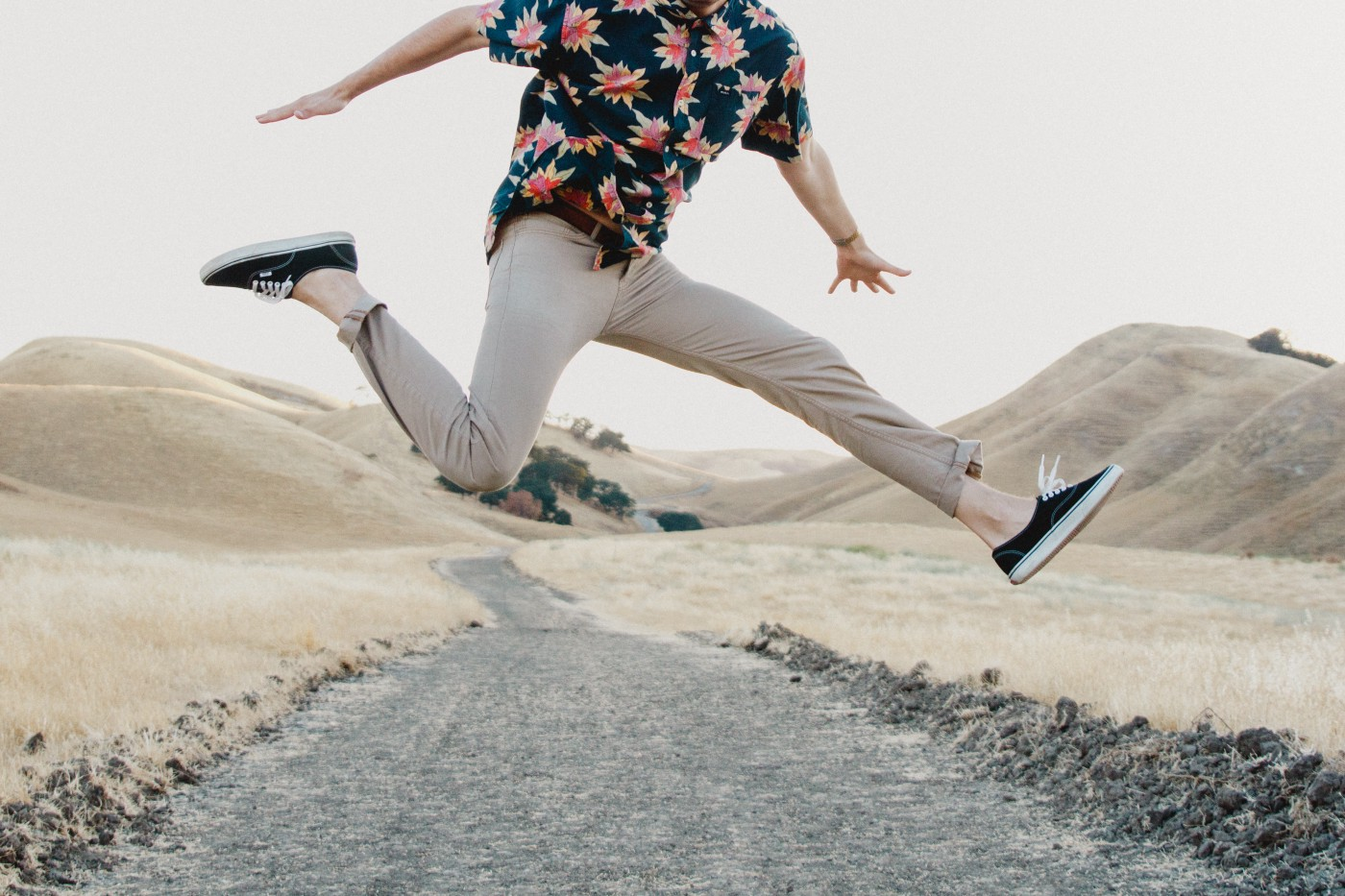A person jumps in the middle of a road.
