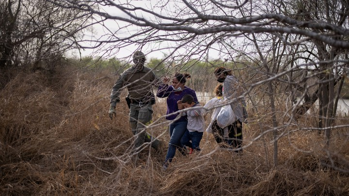 A person in military fatigues forcibly guiding two immigrants and their two small children through some brush.