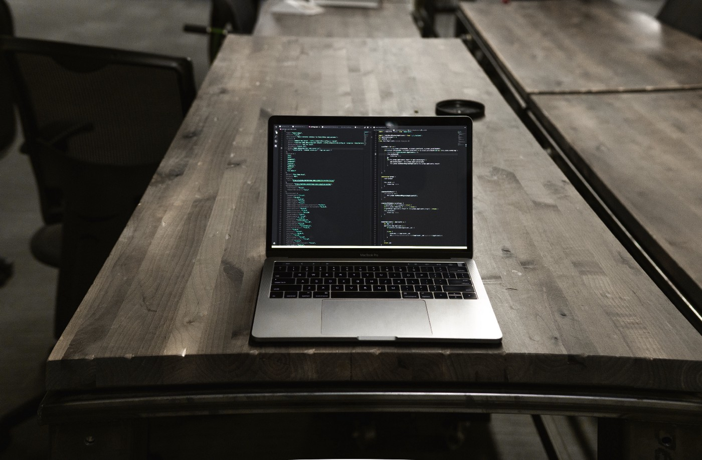A computer sits on a wooden desk, displaying code