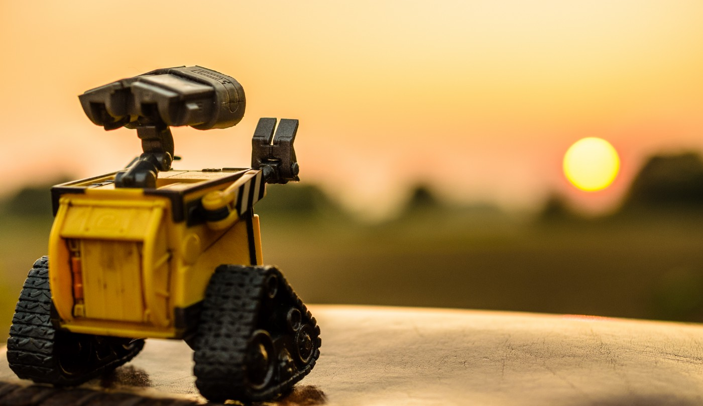WALL-E, seen from behind, waving at the sun as it sets.