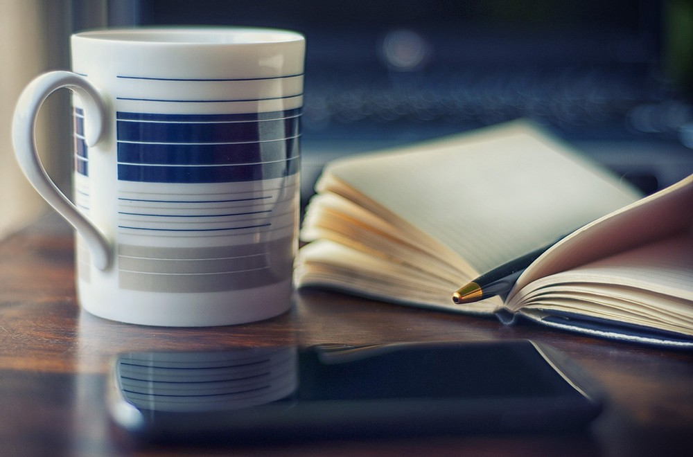 A coffee mug sits beside an open notebook with a pen resting in it, all on a wooden desk.