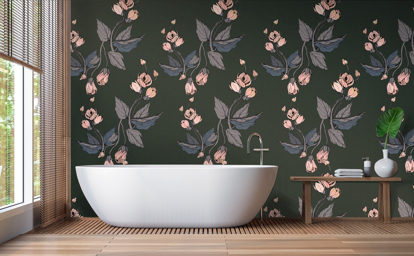 Photo of a large white porcelain bathtub with a side table displaying a potted green leaf, stacked folded hand towels, and a soap dispenser. To the left of the bathtub is a large window with pull-down bamboo blinds, and featured in the background is Kale Tree's Abutilon wallpaper in Midnight Forest. Wallpaper has a dark green background with large pastel pink Abutilon flowers with cool grey leaves.