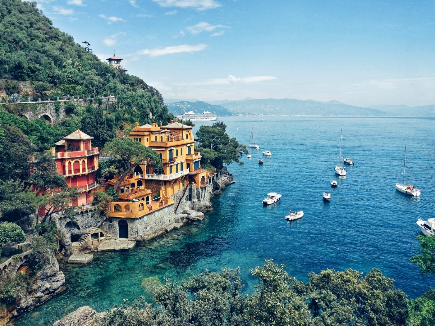 Large yellow mansion perched on a cliff overlooking an inlet on the sea near Portofino. There are many small boats moored and mountains can be seen in the distance.