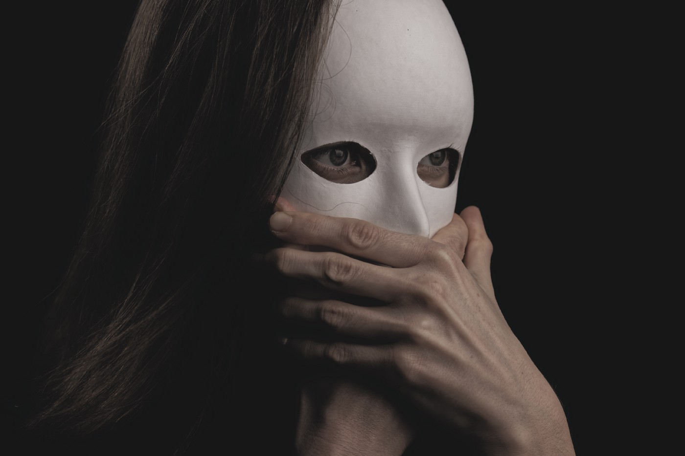 A young brunette woman with long hair is wearing a white cardboard mask, hiding her entire face. But her eyes show through cut out eye holes. They are staring widely at something off-camera. Two unidentifiable hands are grasping where her mouth ought to be, stopping her from speaking. Allodoxaphobia: the fear of hearing others' opinions. My phobia stopped me from speaking out against child abuse. I was unable to confront an abusive parent in public. What would you have done in my situation?