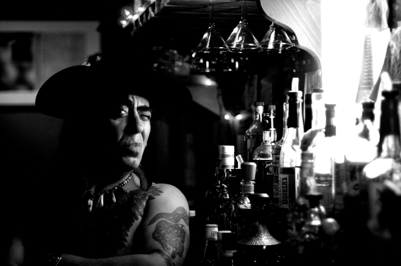 Black and white image of a Native American man sitting at a bar.