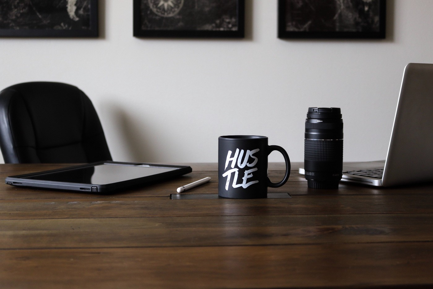 """A mug on a desk next to an open laptop with the word """"hustle"""" written on it."""