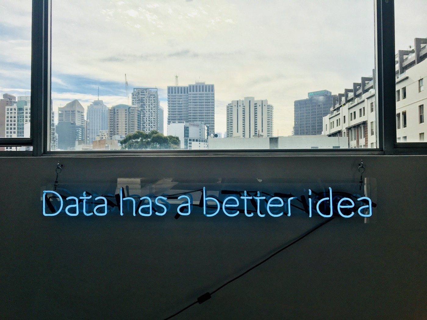 Neon Blue lettering. Phrase is 'Data has a better idea'. It is below a window which has a view of a city skyline behind it.