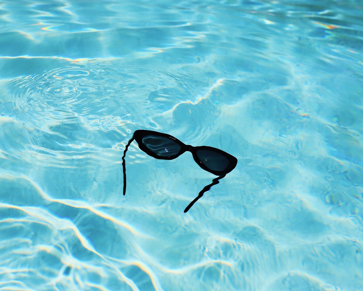 Sunglasses floating in bright blue water.