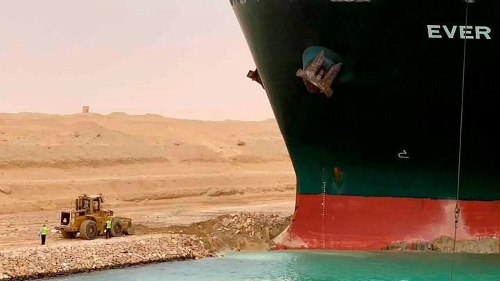 The hull of the Ever Given stuck on the shore of the Suez Canal in front of a relatively tiny excavating machine.