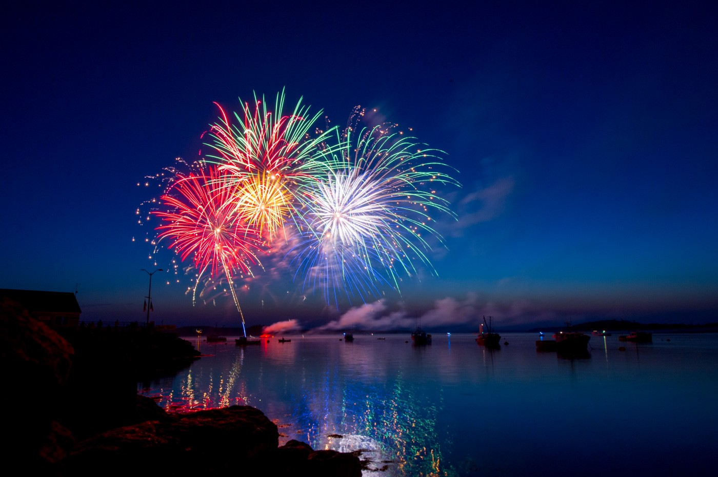 Picture of fireworks in red, gold, purple, and green over a lake.