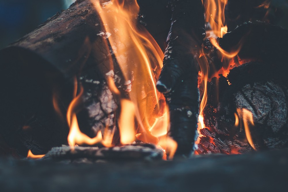 A campfire burns orange on black and red coals.