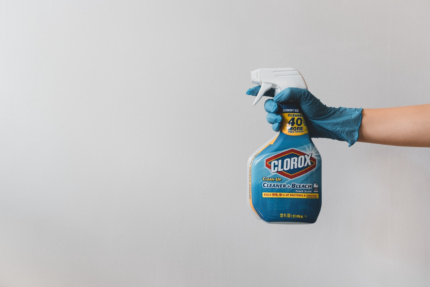 A gloved hand with a bottle of Clorox spray pointed at something