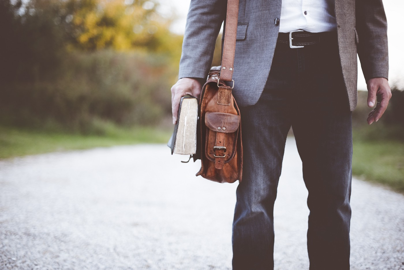 sophisticated guy holding a book and carrying a leather bag