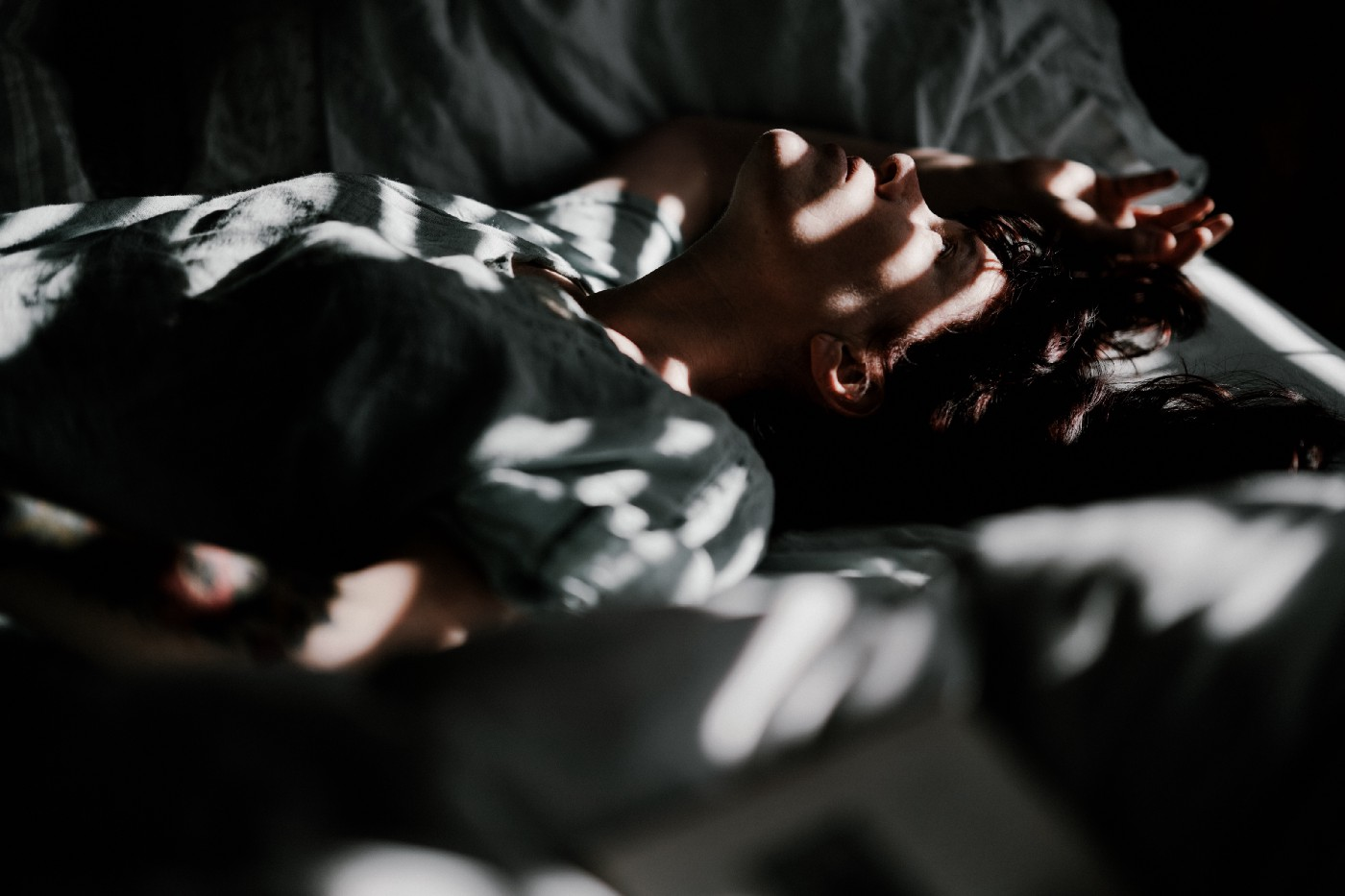 A young woman is sleeping on a bed with the sun filtering through the blinds on her window