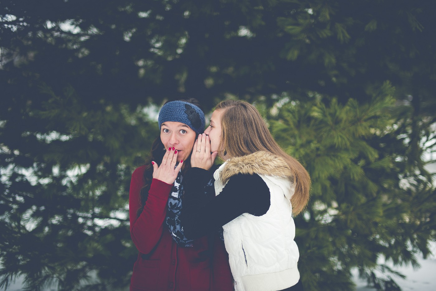 A woman telling another woman a secret