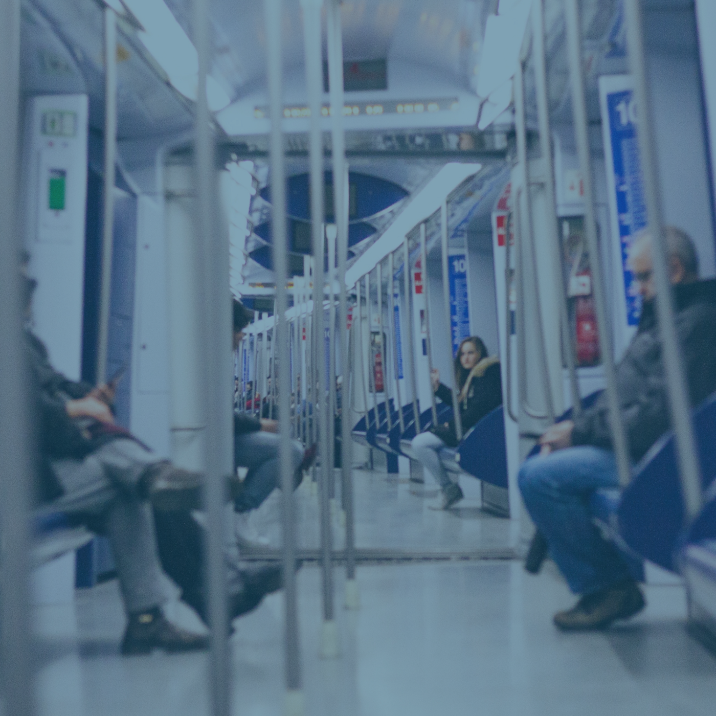 image shows the inside of a subway car, viewed down the length with a few passengers onboard