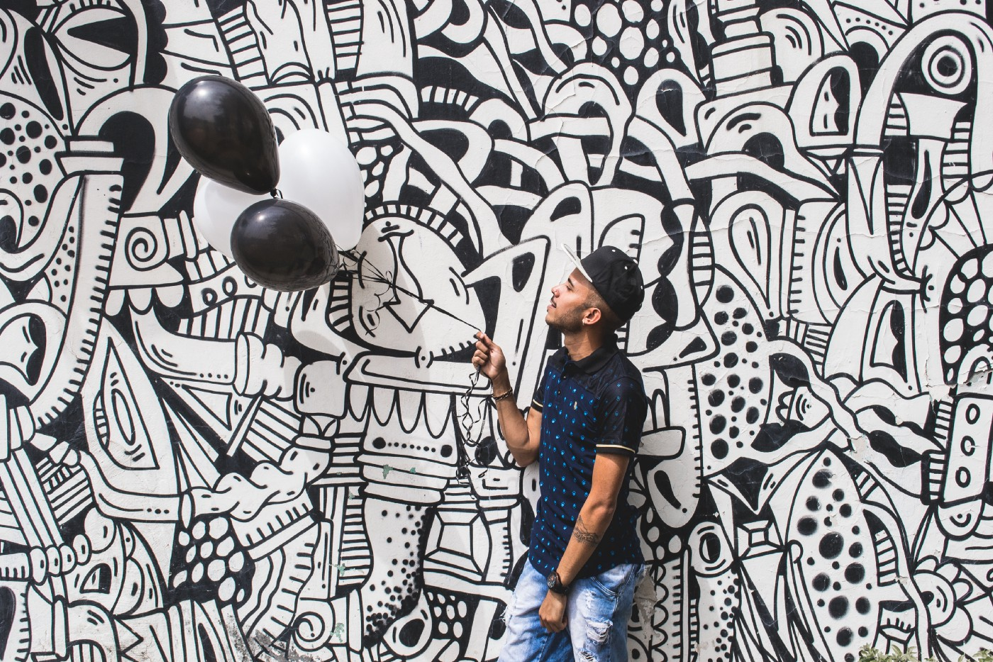 Image of mural and man holding balloons in front of it