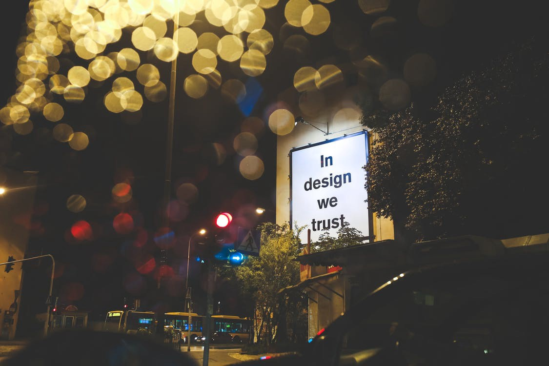 """A close up of a billboard saying """"in design we trust"""""""