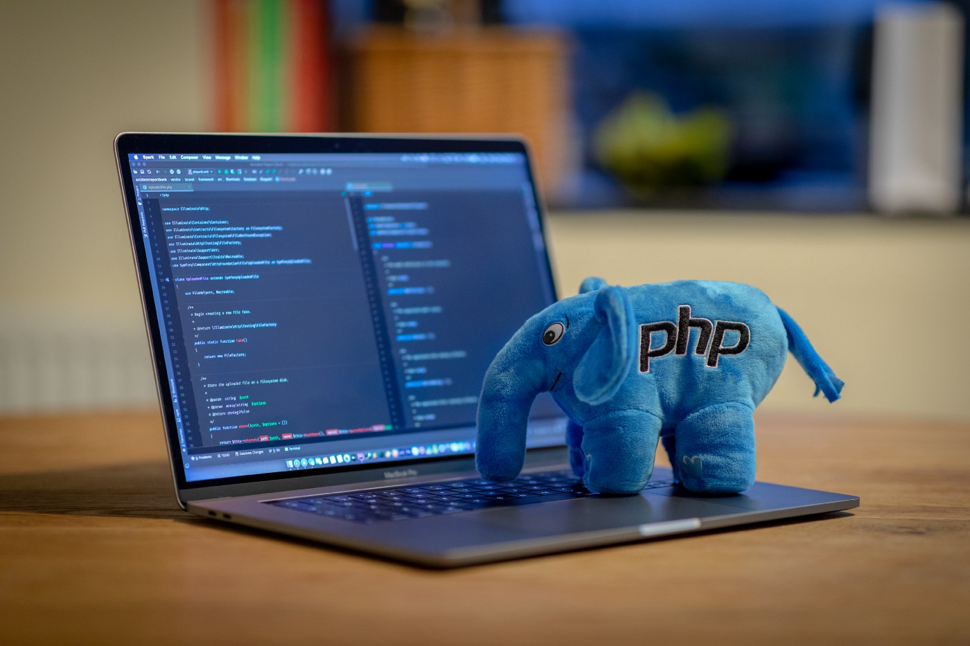 small blue toy elephant with the letters PHP on its side, in front of an open notebook computer