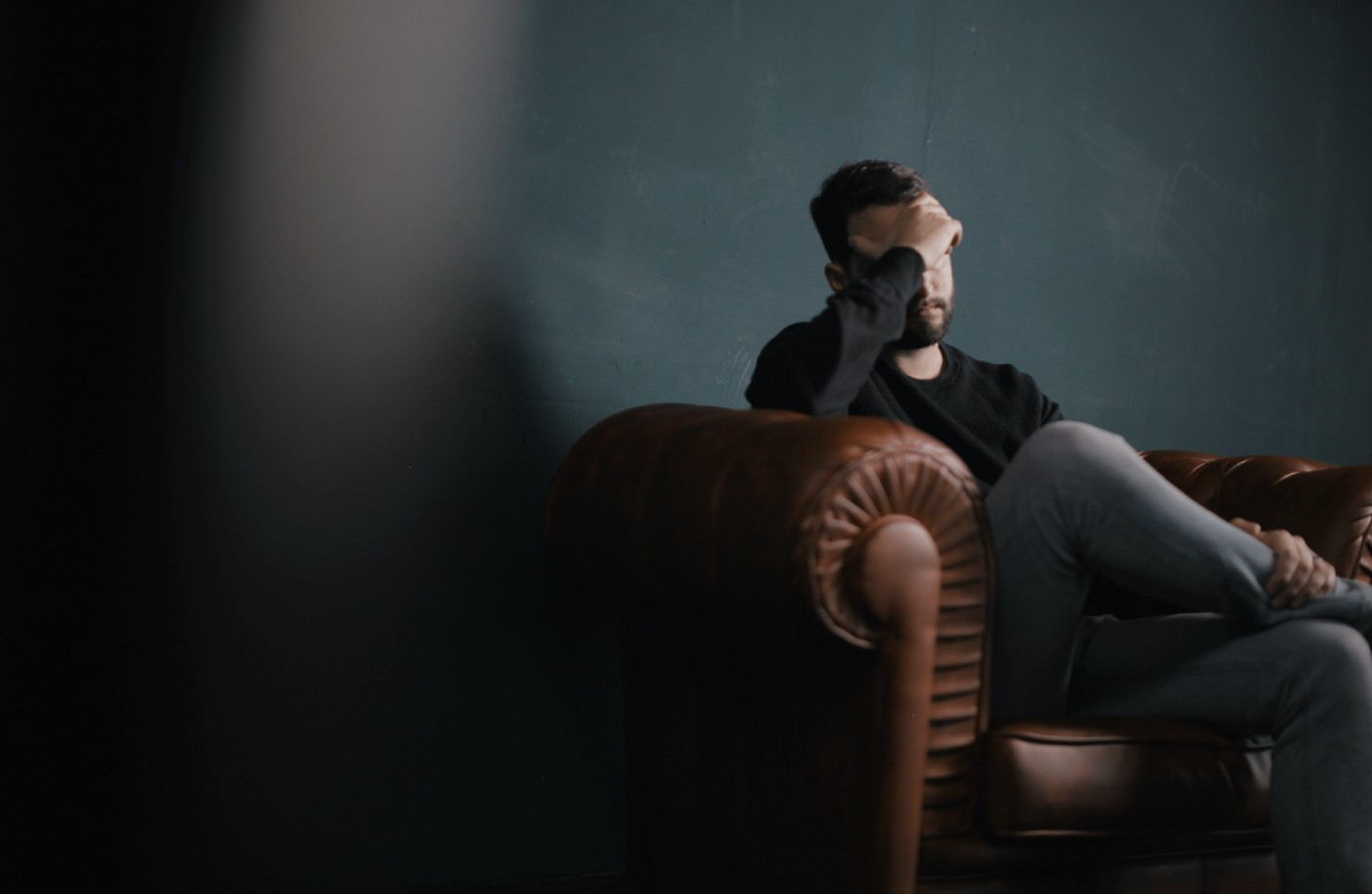 man sitting on a brown leather couch with his head in his hand