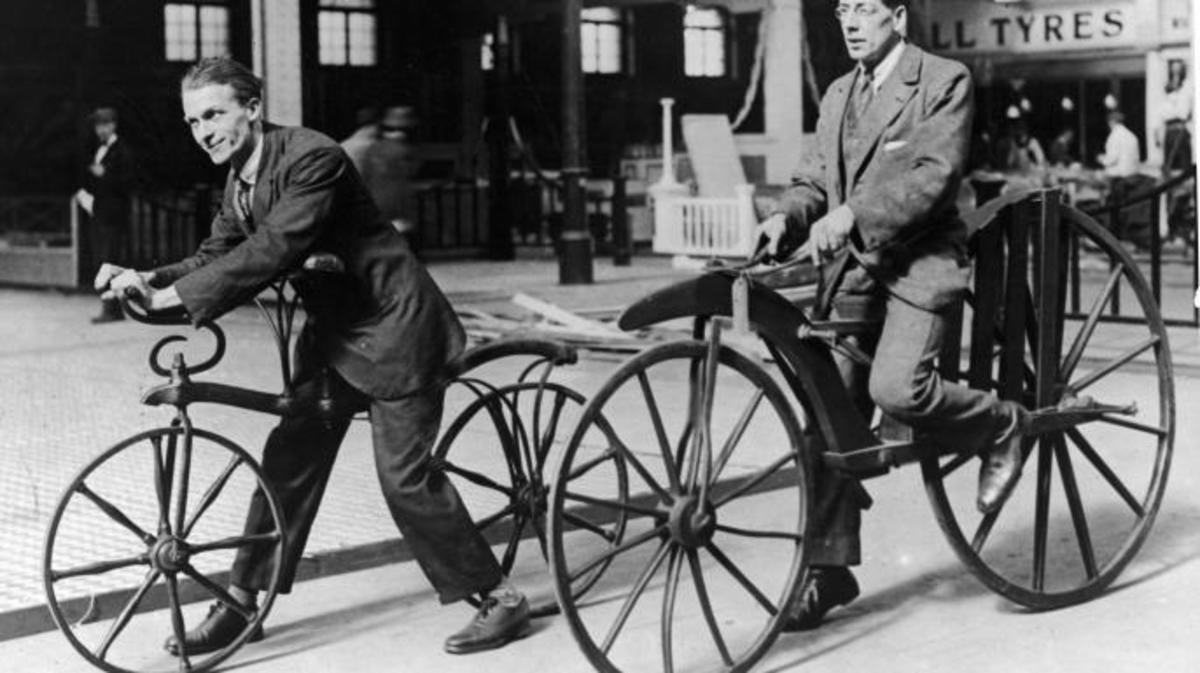 Two men ride on early bicycles known as the Hobby Horse and 'boneshaker'. The Hobby Horse was invented by Karl Von Drais in 1818 and was operated by kicking against the street. By 1863, cranks and pedals were added to to create the 'boneshaker'. Herz/Getty Images (Andrews).