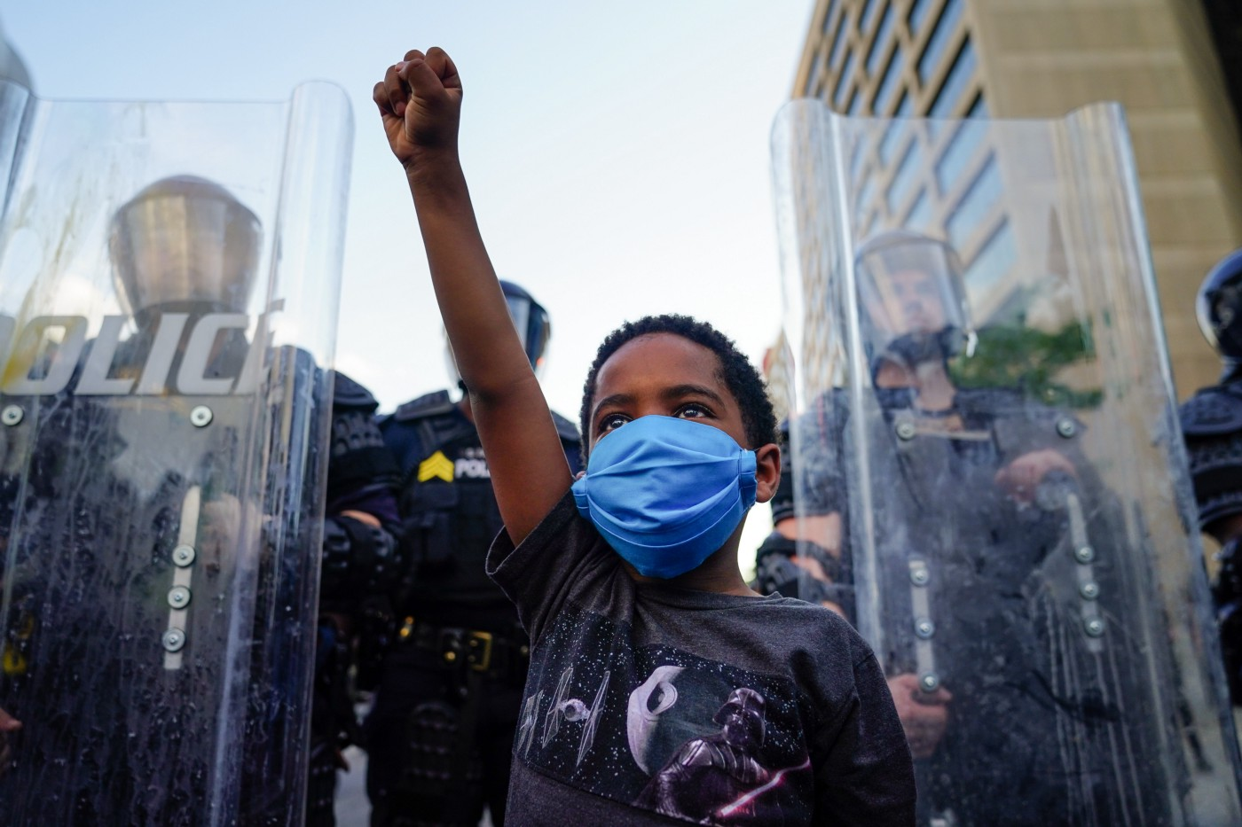 A small Black child raises his fist in front of police.