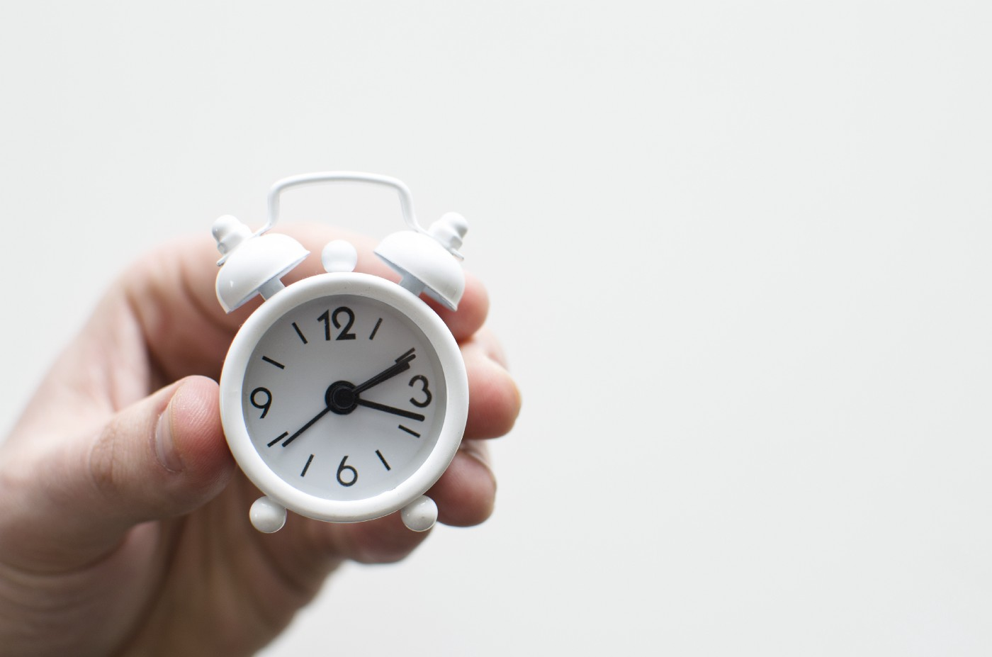 hand holding a small old-fashioned manual alarm clock