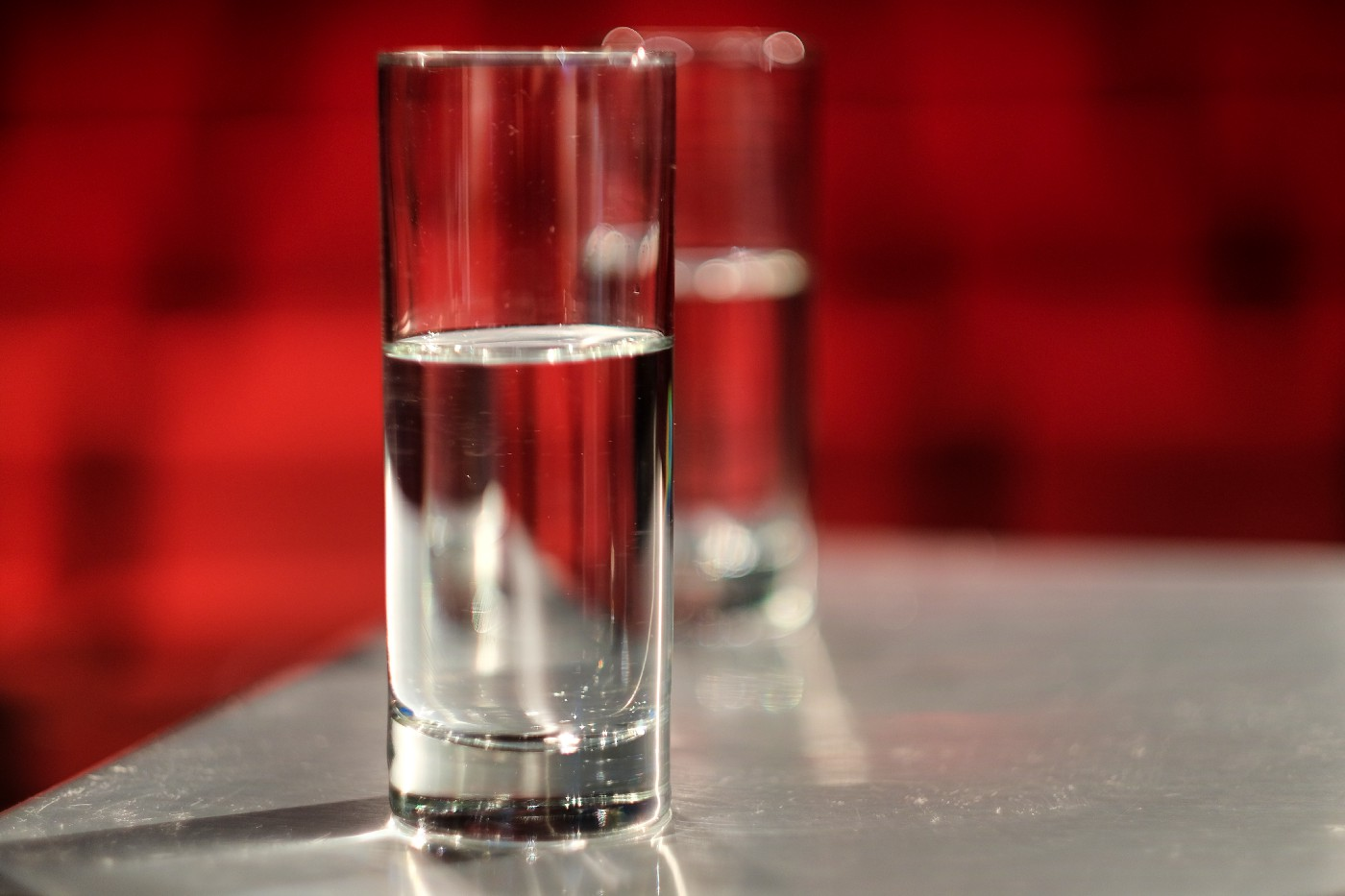 Two transparent glasses which are half filled with water kept on a table.