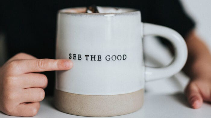 "Finger pointing to a mug that says ""See the good"""
