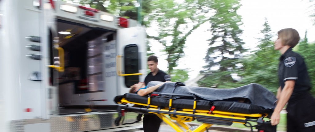 Two emergency responders lifting stretcher into rescue vehicle