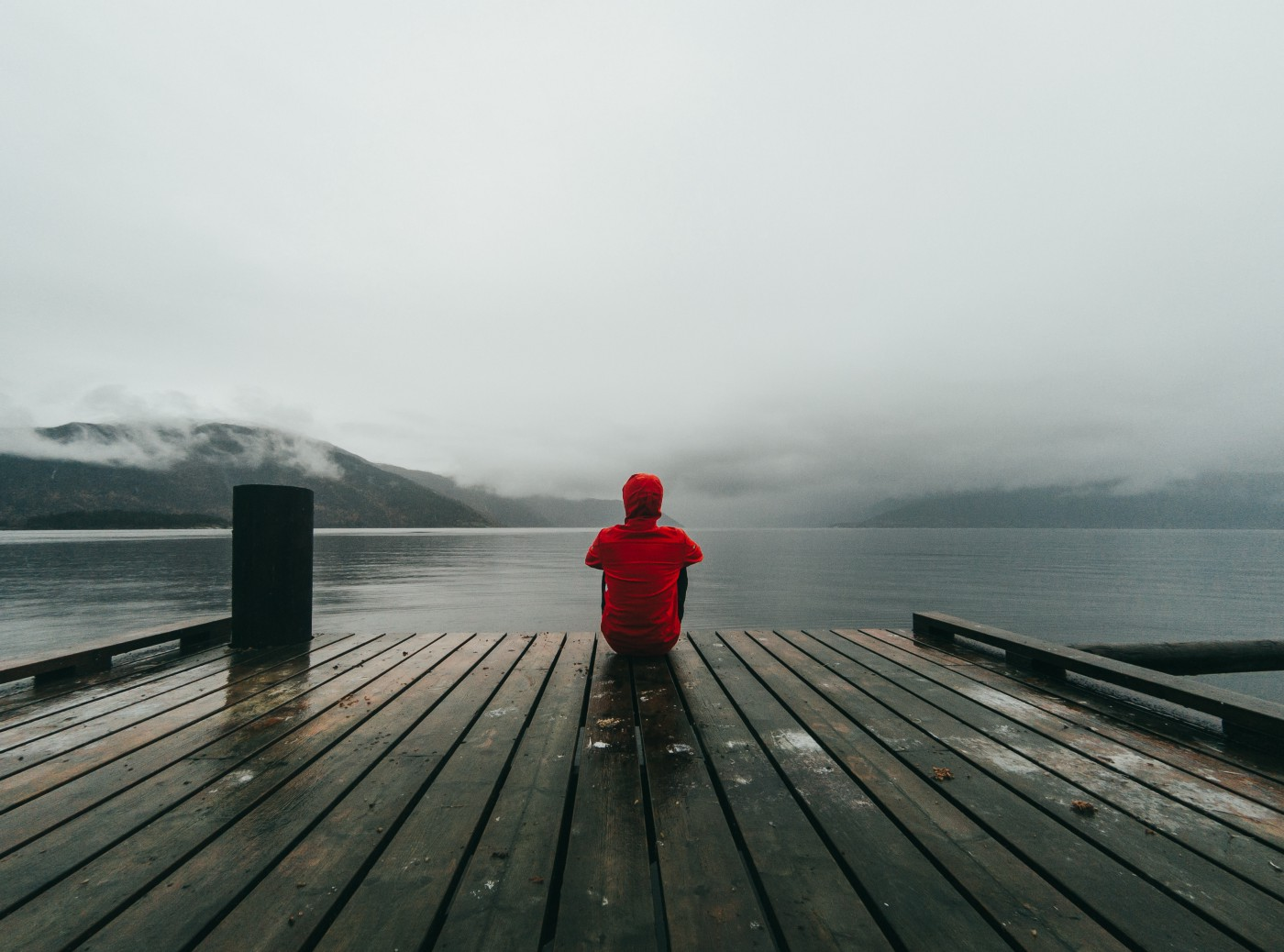 A person sitting on a wintry dock overlooking the water.