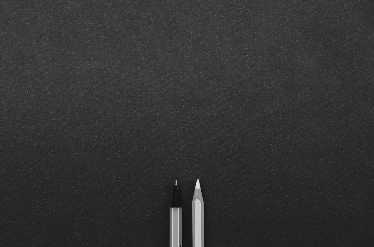 Two pens on a black surface.