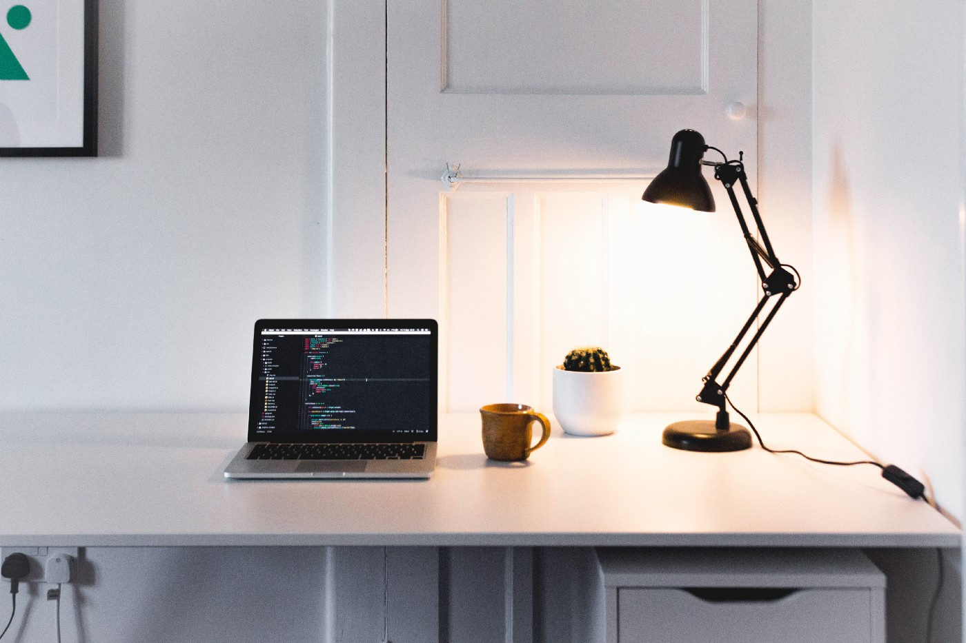 Laptop on top of a white desk, with code on the screen, next to an orange mug, a cactus and a black lamp