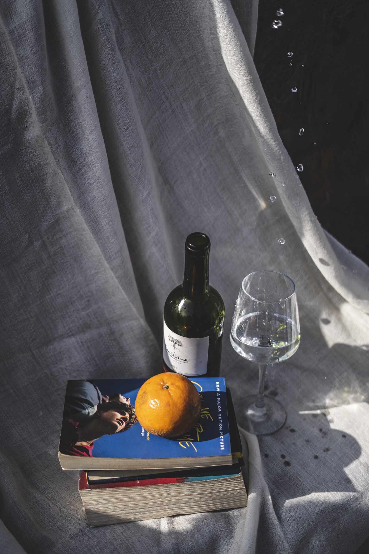 A bottle and wine glass with a stack of books