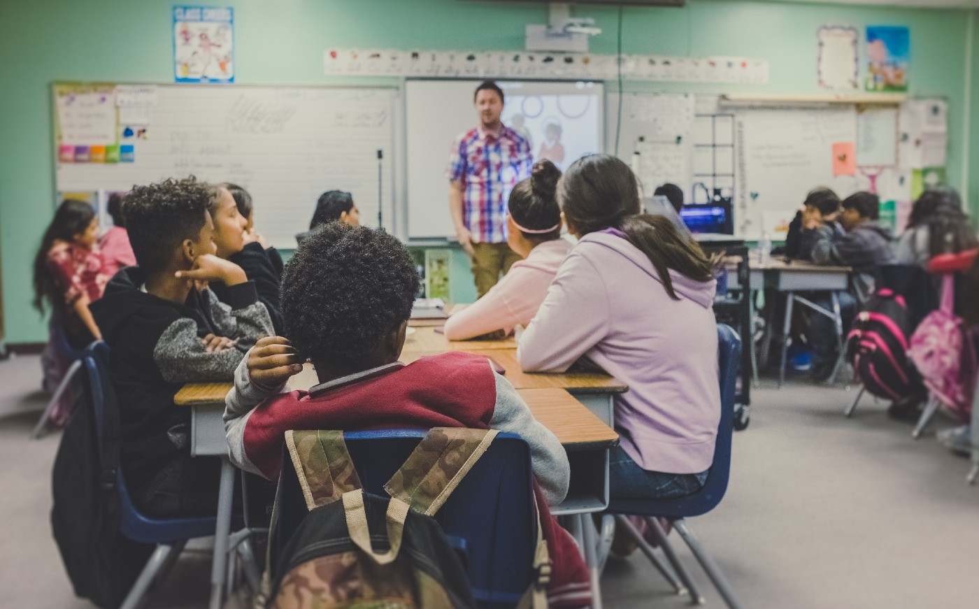 A teaching is standing in front of a class of attentive young students.