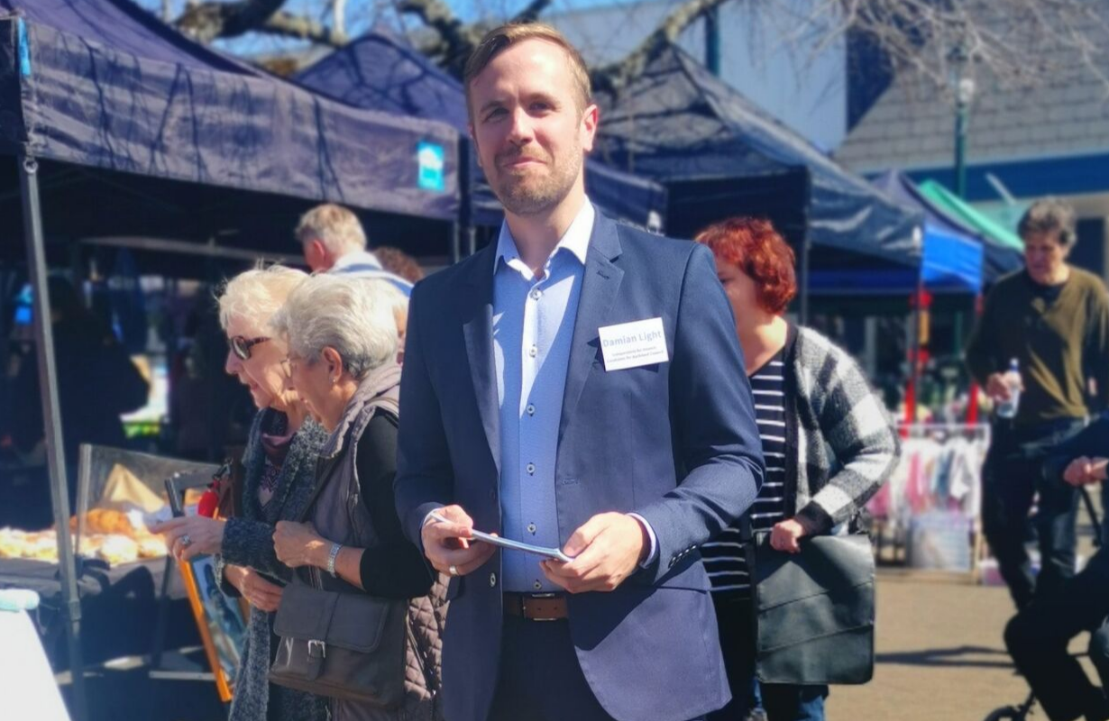 Damian at a local market looking to camera, smart suit jacket and a name badge