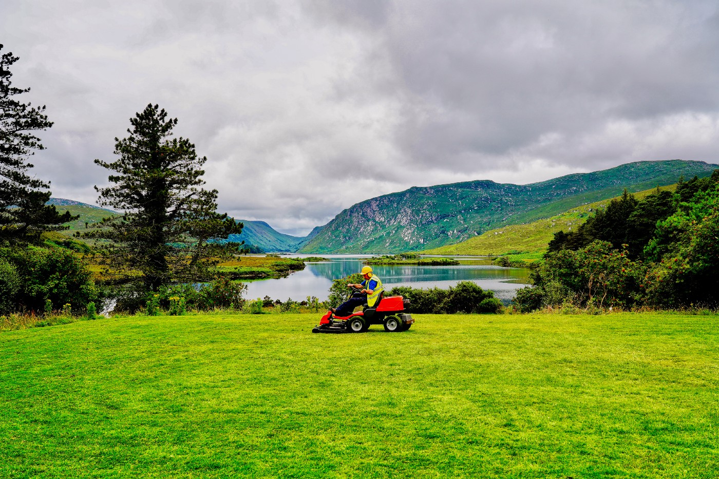A man on a riding lawnmower over lush grass with a lake and mountain in the background