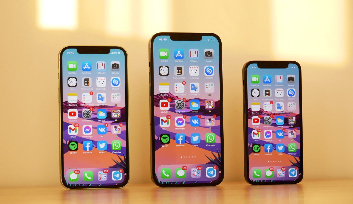 All three iPhone 12 models side by side on top of desk