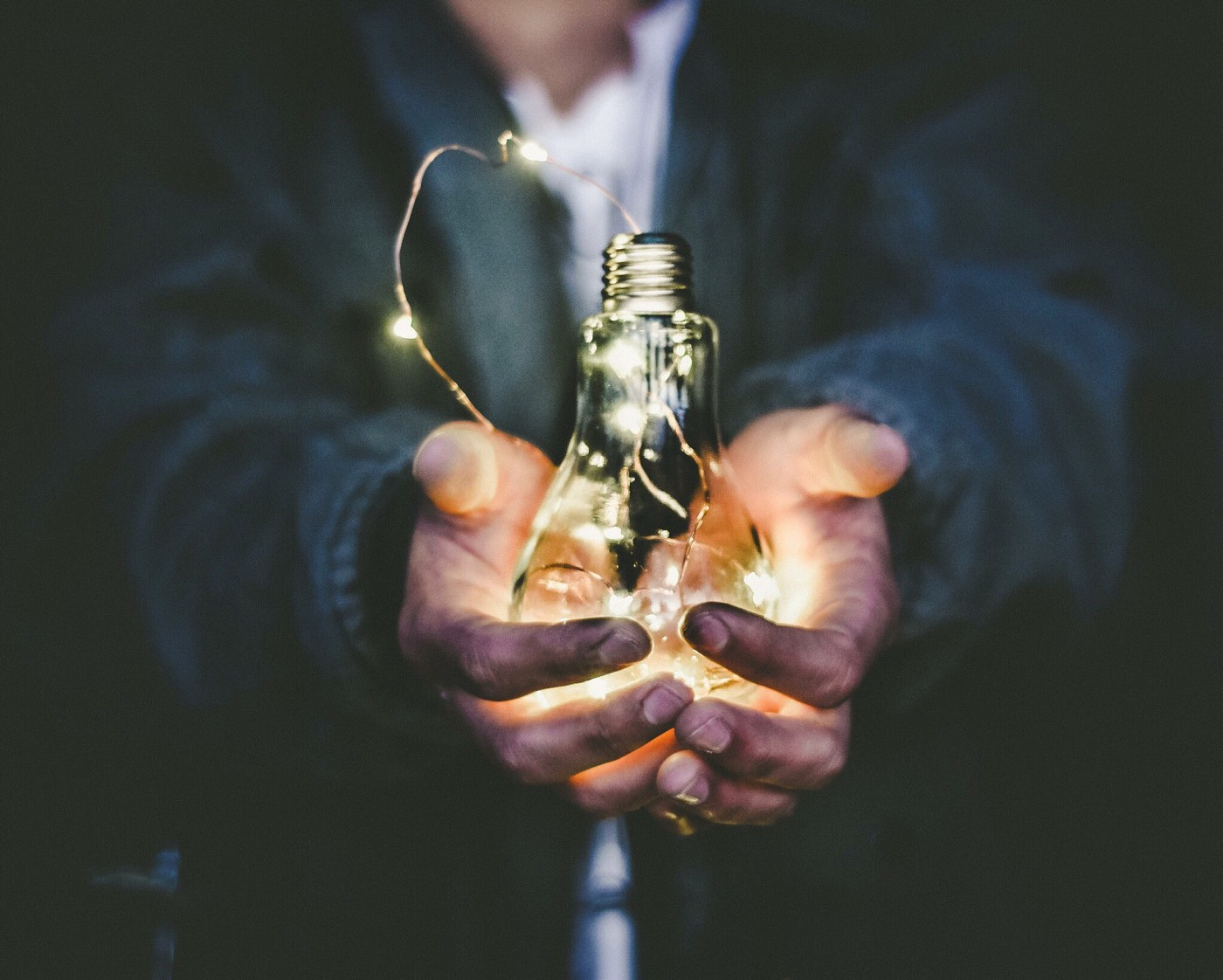 photo of man holding lightbulb in hand; photo on james goydos md 2021 post about mentoring