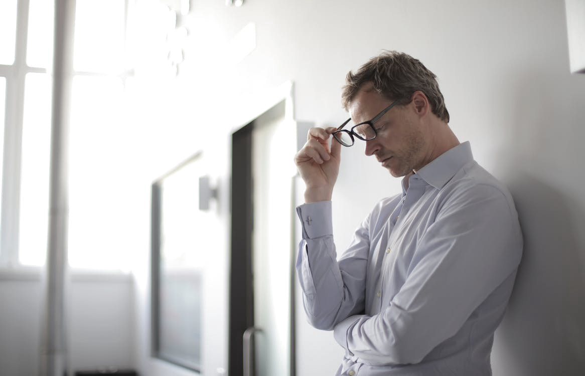 Young man in a light color dress shirt leaning back against a wall in a hallway and talking off his glasses.