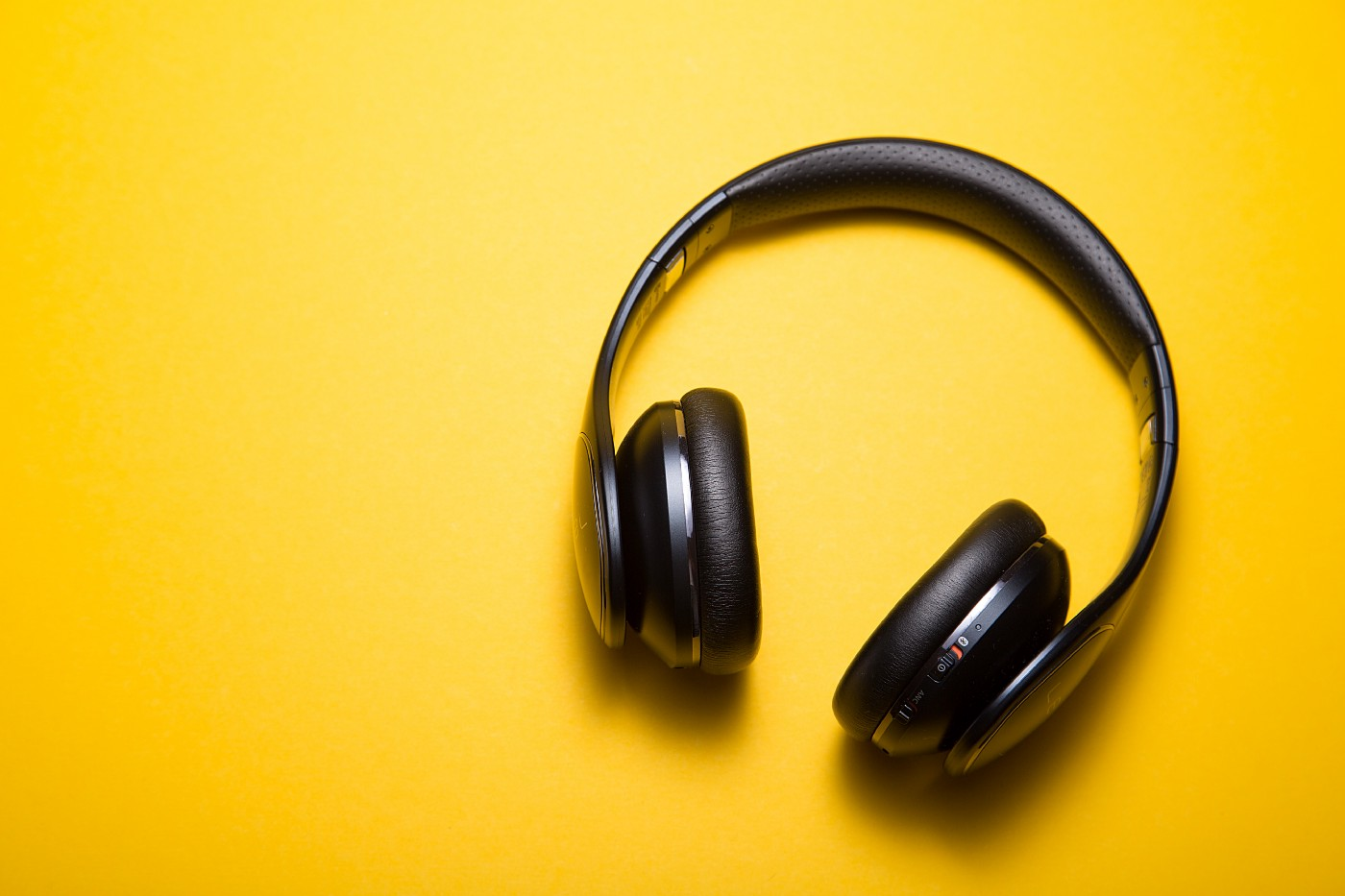 A pair of black headphones against a yellow background