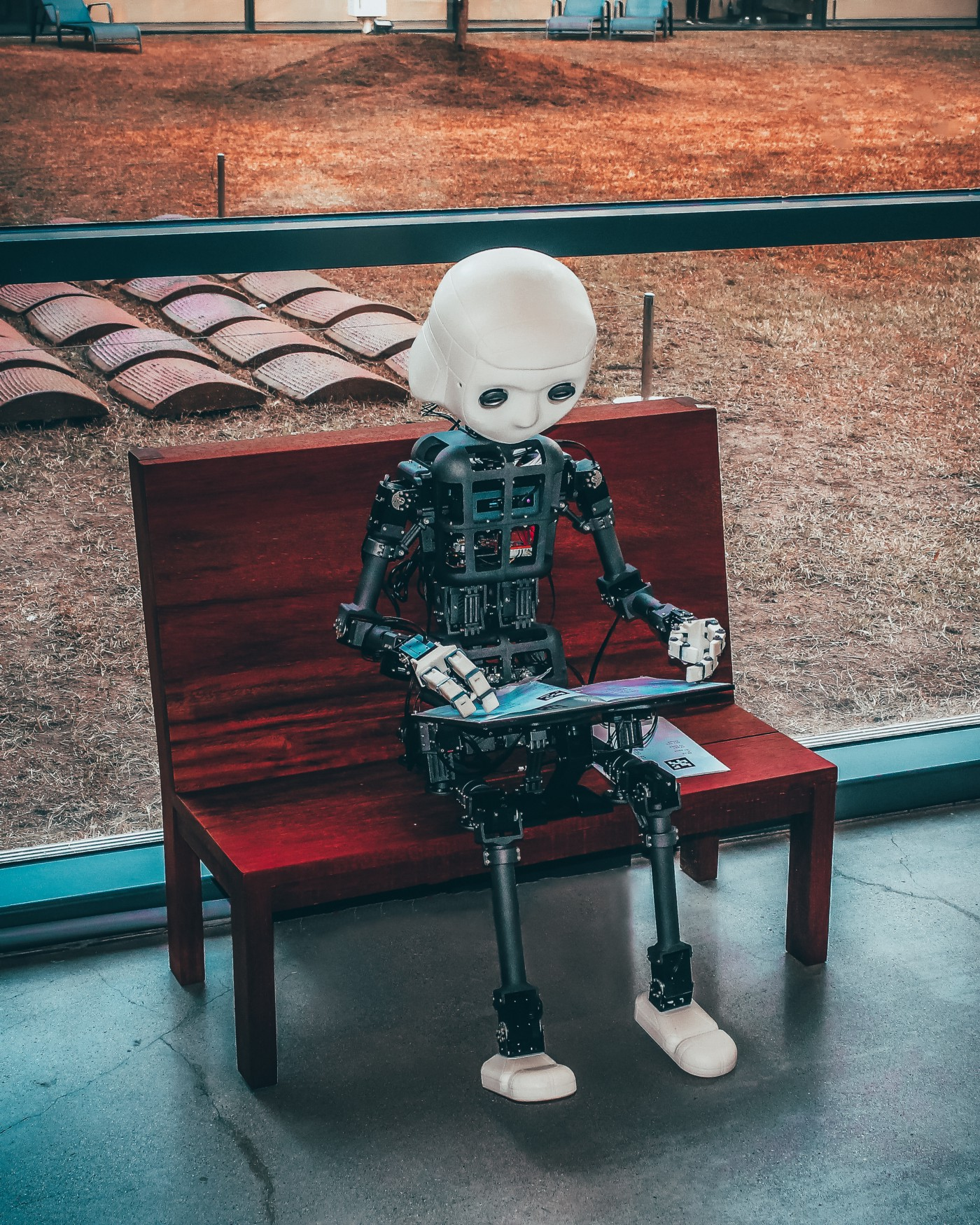 humanoid robot sitting on a bench looking at a laptop