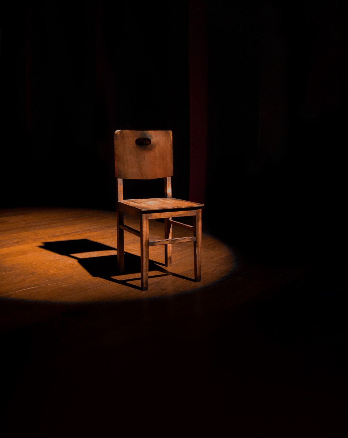 very used wood chair, very straight lines, on a dark stage with spotlight