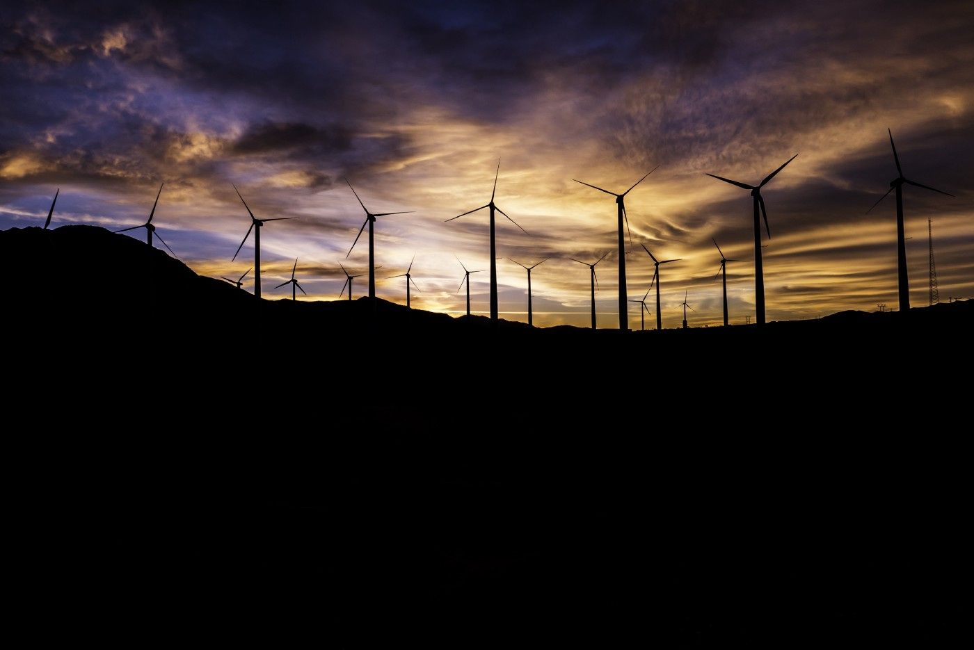 A wide shot of a wind farm with sunset in the background.