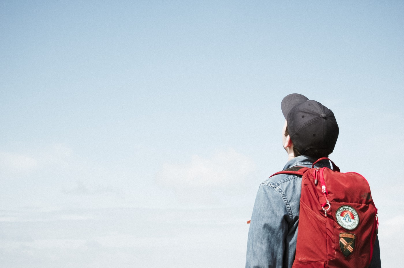Person looking at the sky, holding a backpack