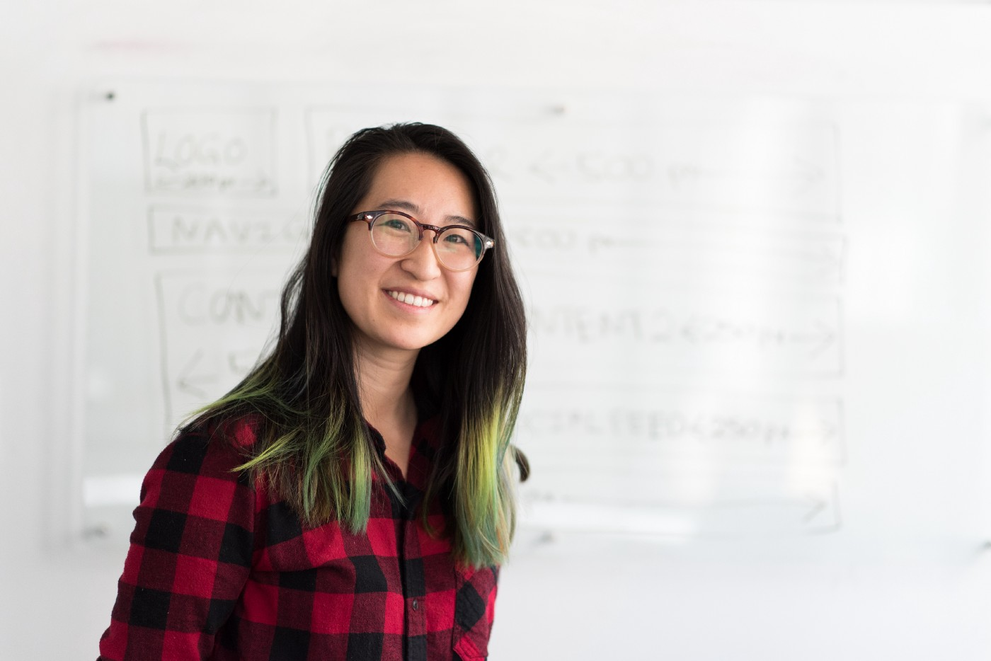 Smiling woman with long, green-tipped dark hair and horn rim glasses, standing in front of a white board