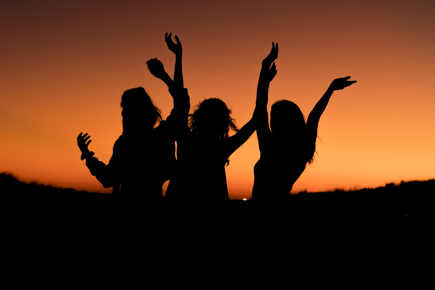 Silhouettes of three women covered in black shadow are standing outside in front of a sandy hill during a summer evening. They are waving their hands in the air in celebration in front of a beautiful pink and orange burst sunset. Win $5,000 per week writing fiction this summer. Vocal Media has launched SFS: The Summer Fiction Series. 8 weekly short-fiction writing challenges to jump-start our creativity, with $52,000 in prizes.