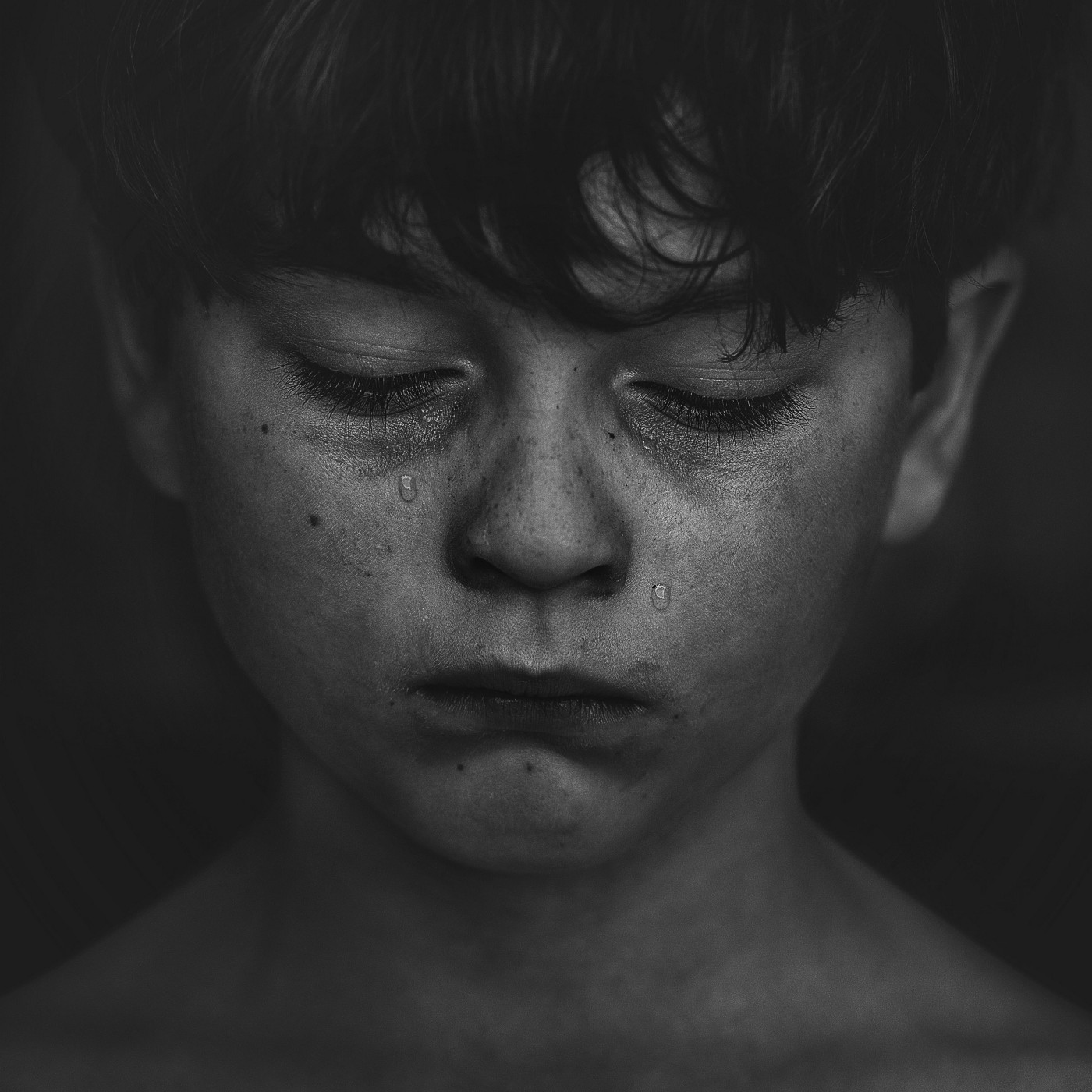 A child weeping in the dark shadows of his abuse.
