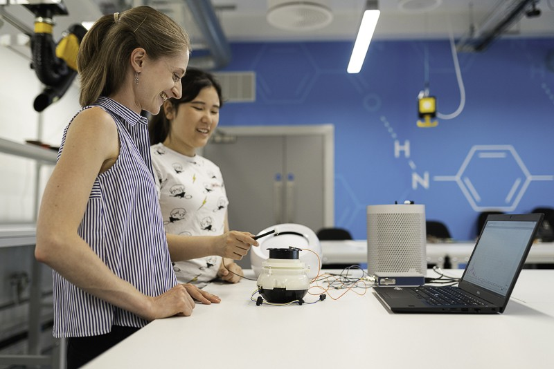 Two young women working on a robotics project in a lab.